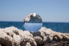 Glaskugel auf einem Tau am Meer